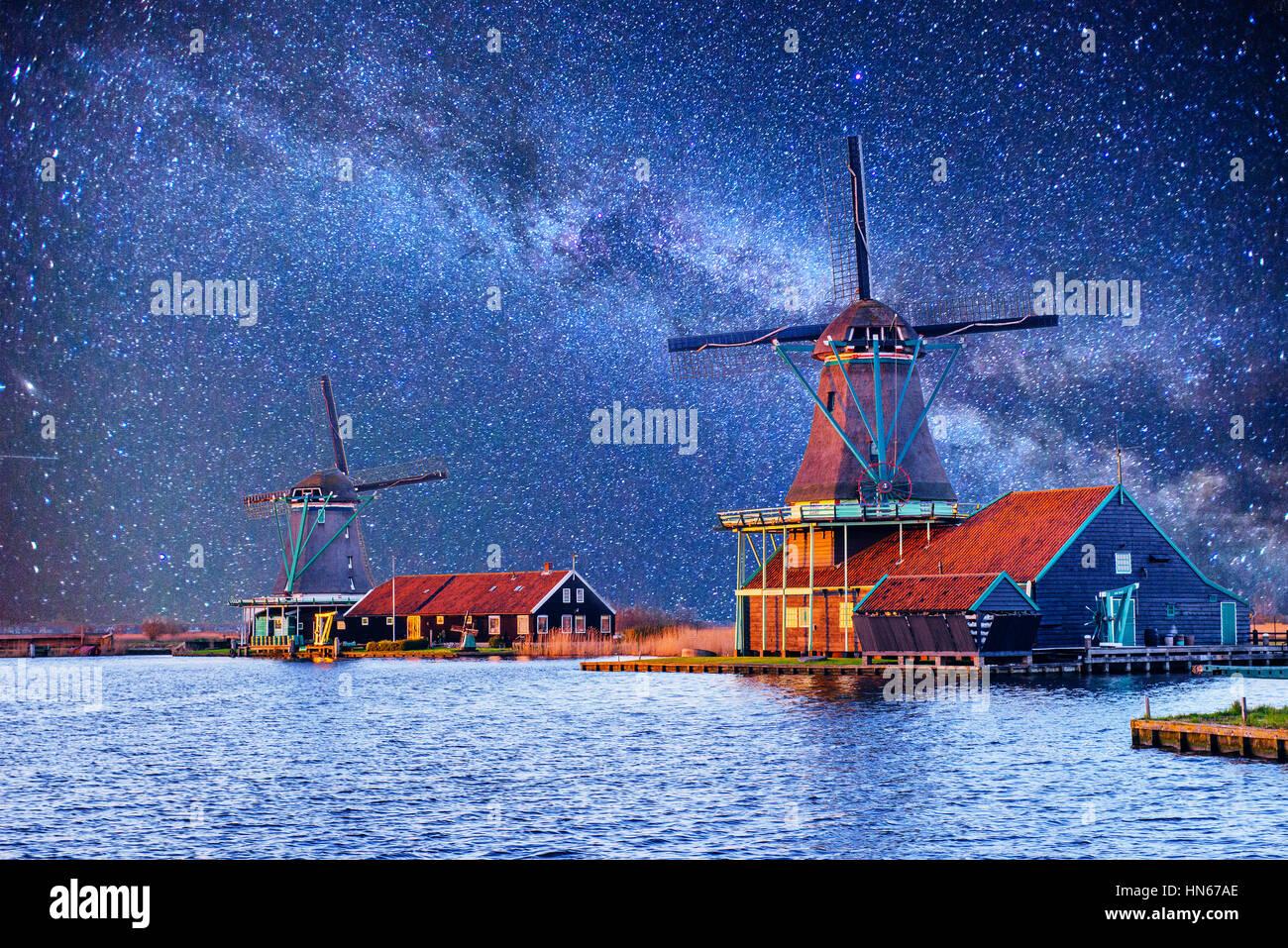 Cielo estrellado sobre molinos holandeses desde el canal en Rotterdam. Imagen De Stock