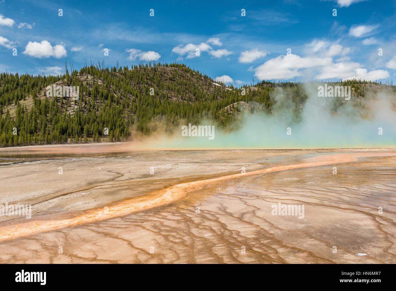 Aumento de vapor y neblina azul de Grand Prismatic hot spring en Midway Geyser basin en el Parque Nacional de Yellowstone con patrones bacterianos rojo Foto de stock