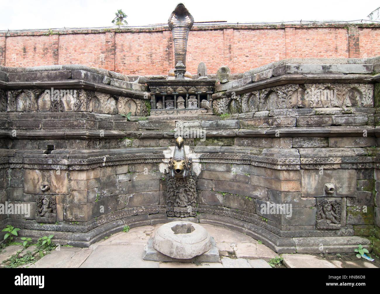 Pared del estanque de un templo en Katmandú mostrando tallas en piedra, una protección de rey cobra y una boquilla de agua de bronce tallado Foto de stock
