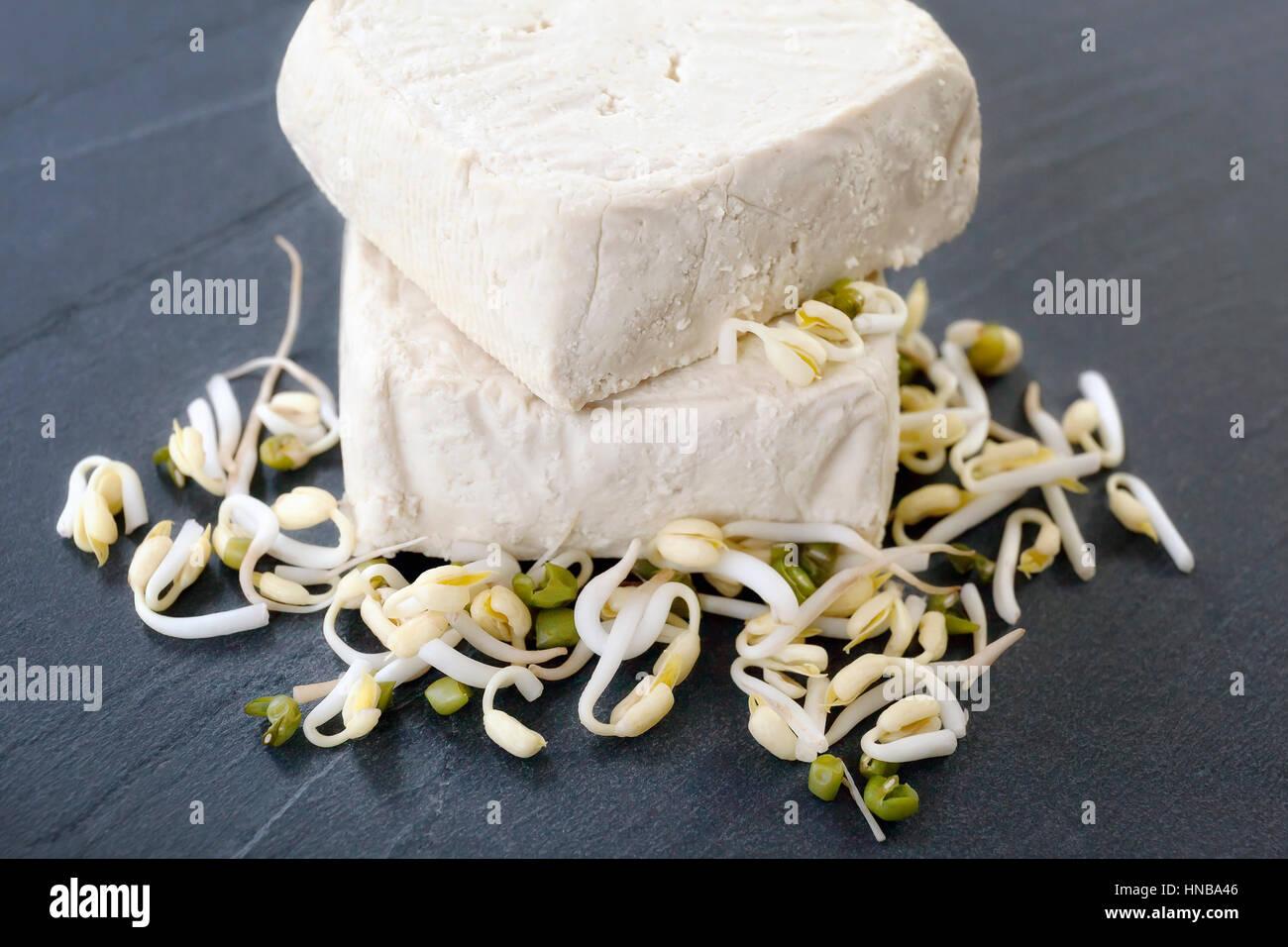 Materias tofu pedazos sobre una base de piedra de la junta y de la soja, la materia prima a partir de la cual obtenemos Foto de stock