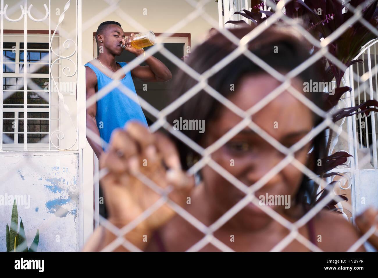 La cuestión social, el abuso y la violencia sobre la mujer, hombre hispano borracho y triste negro mujer llorando Imagen De Stock