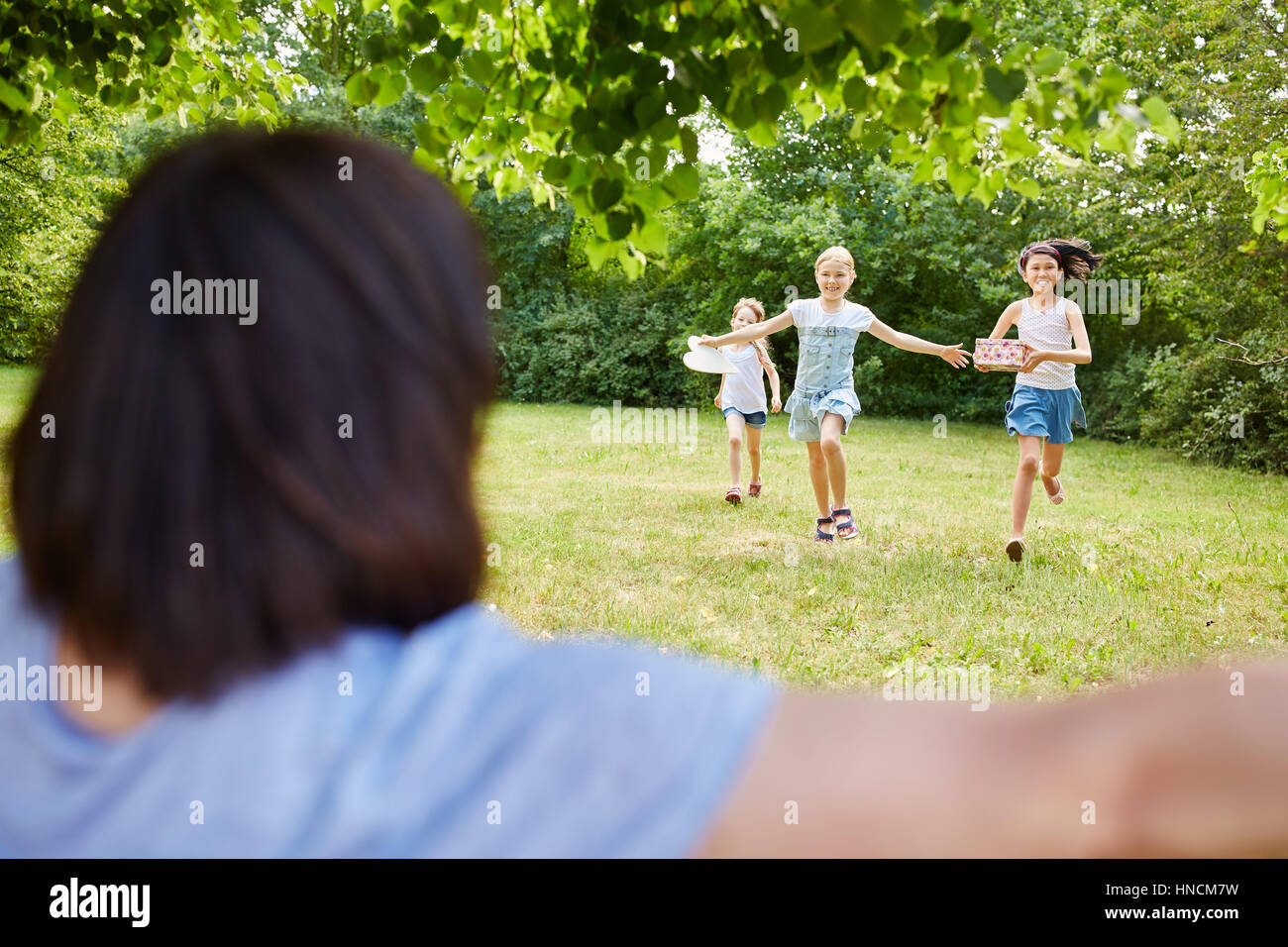 Niños corren a abrazar cumpleaños niño en su fiesta de cumpleaños Imagen De Stock