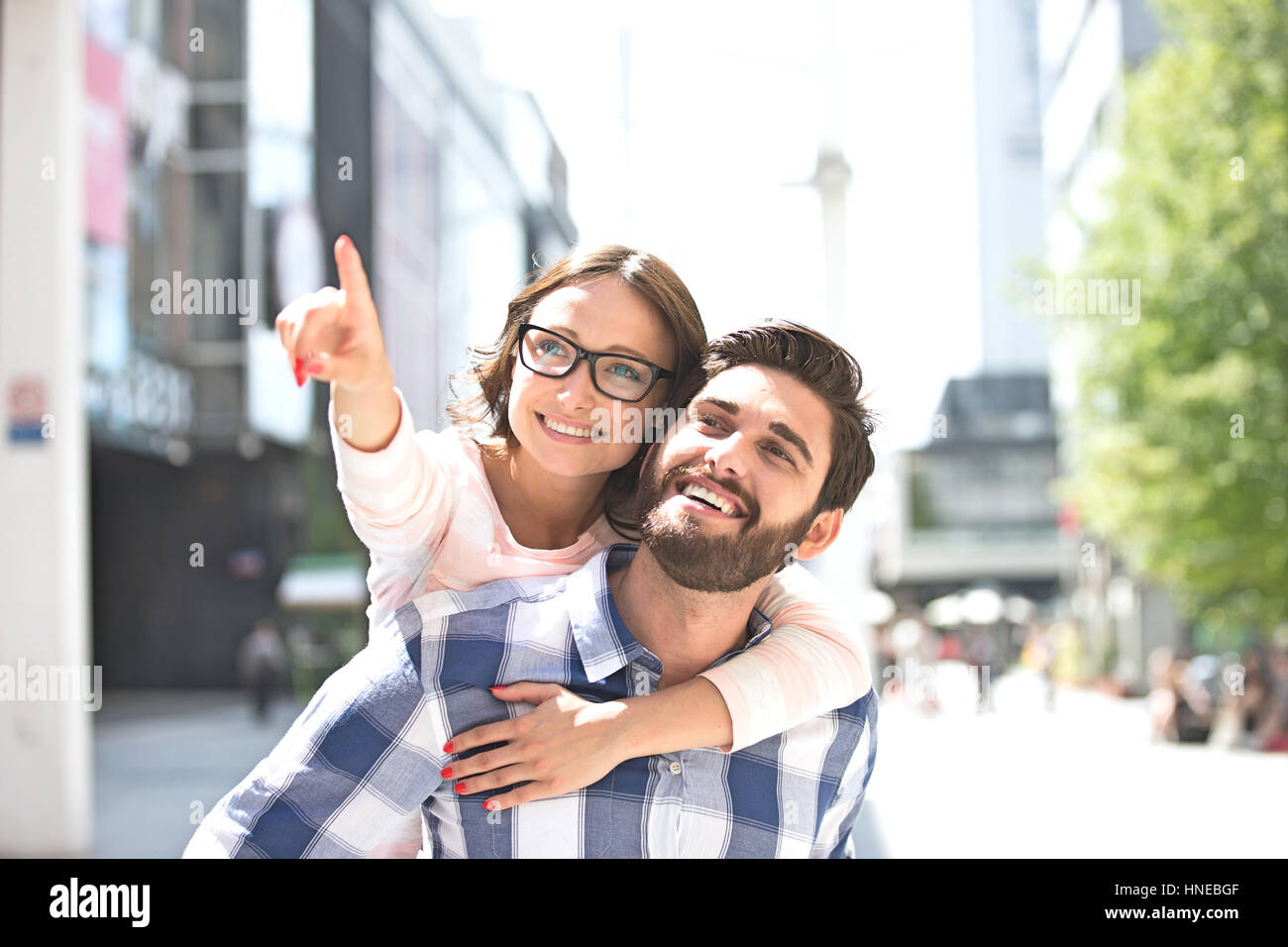 Mujer alegre apuntando hacia fuera mientras disfruta piggyback paseo sobre el hombre en la ciudad Foto de stock