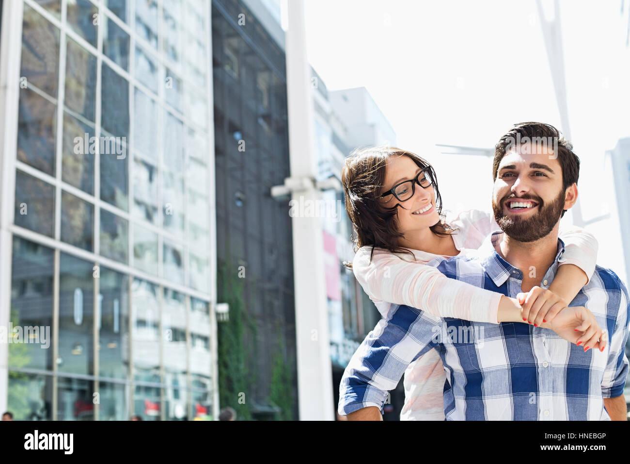 Hombre feliz viaje piggyback dando a la mujer en la ciudad Foto de stock