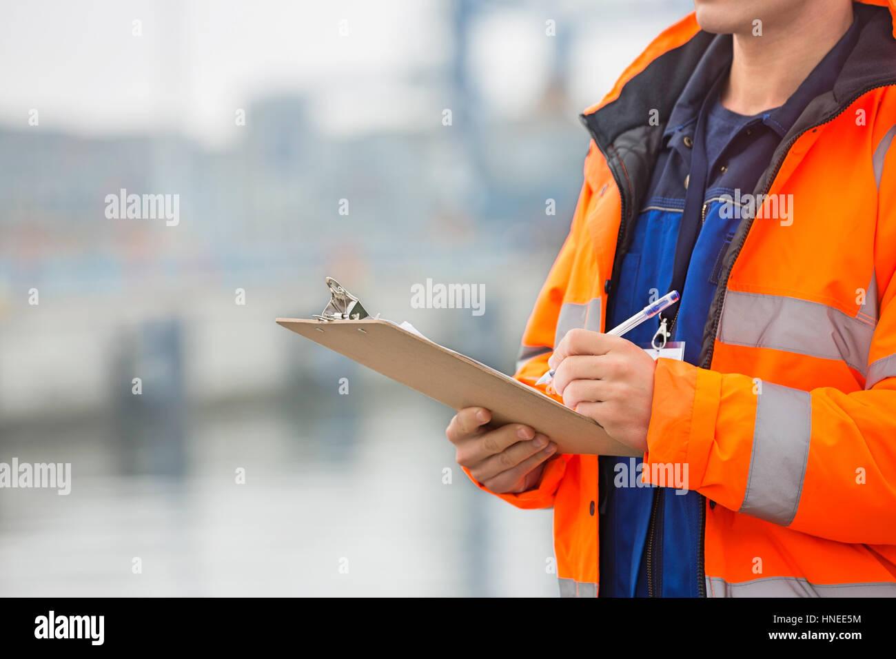 Sección media de un hombre adulto medio escrito en el portapapeles en el patio de envío Foto de stock