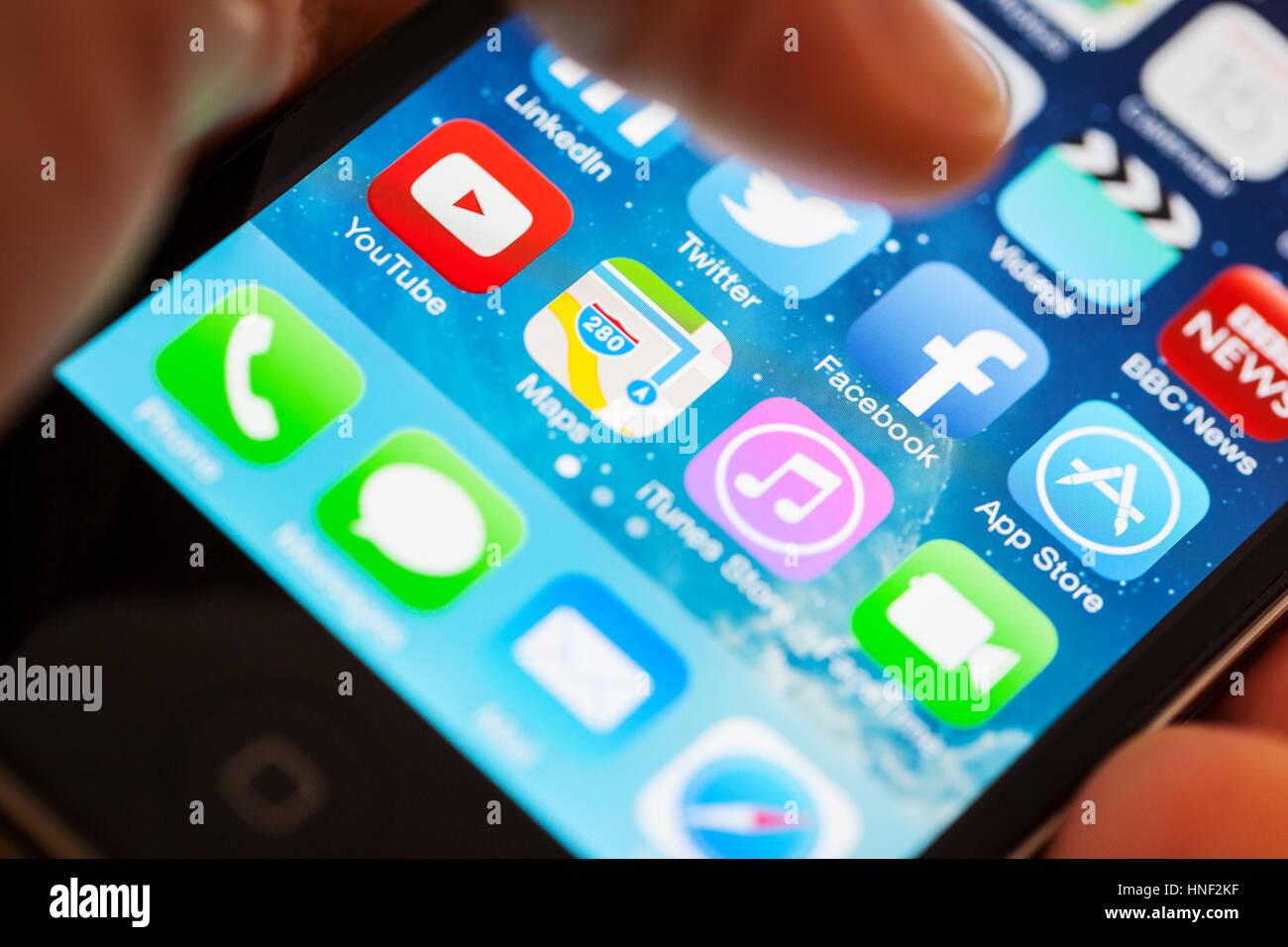 BATH, Reino Unido - 15 de enero de 2014: Cerca de un Apple iPhone 4S Screen con un pulgar del hombre flotando encima Imagen De Stock
