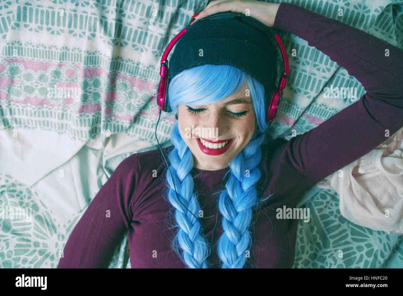 Alternativa adolescente con el pelo azul listenig música Foto de stock