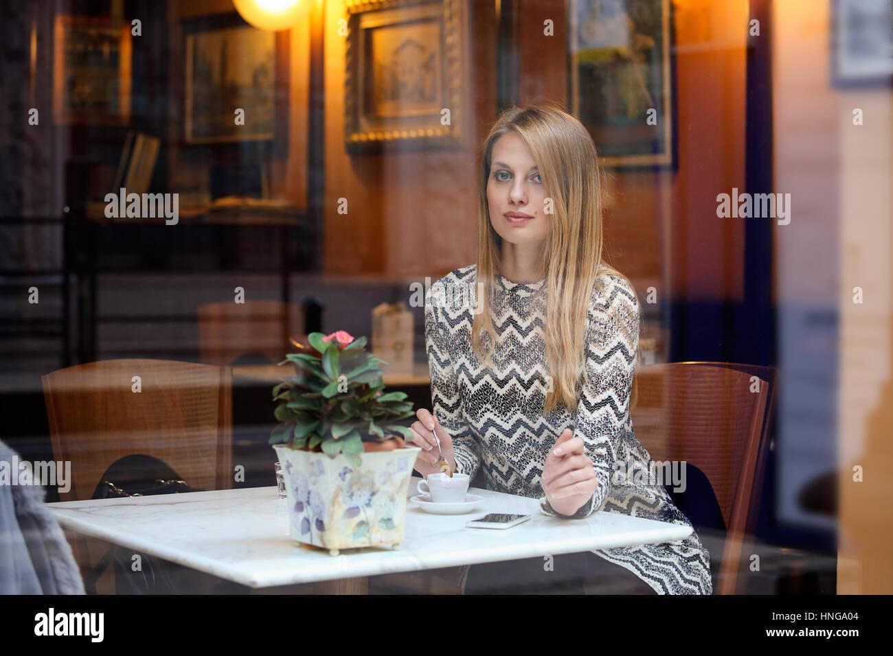 Hermosa mujer elegante en una elegante cafetería de la ciudad. El estilo de vida urbano Foto de stock