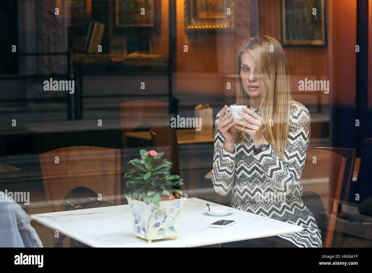 Mujer con una taza de café. Filmación urbana a través de la ventana Imagen De Stock