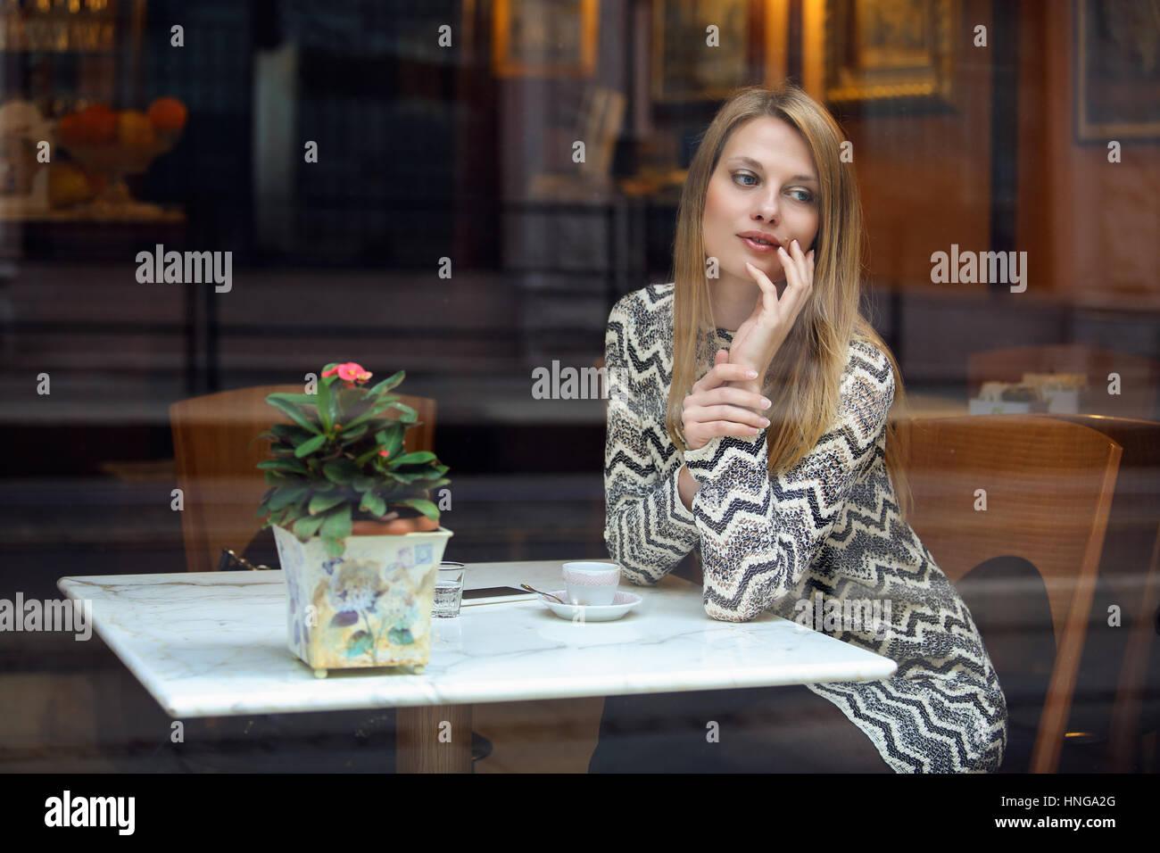 Elegante joven en un elegante café. Filmación urbana Imagen De Stock