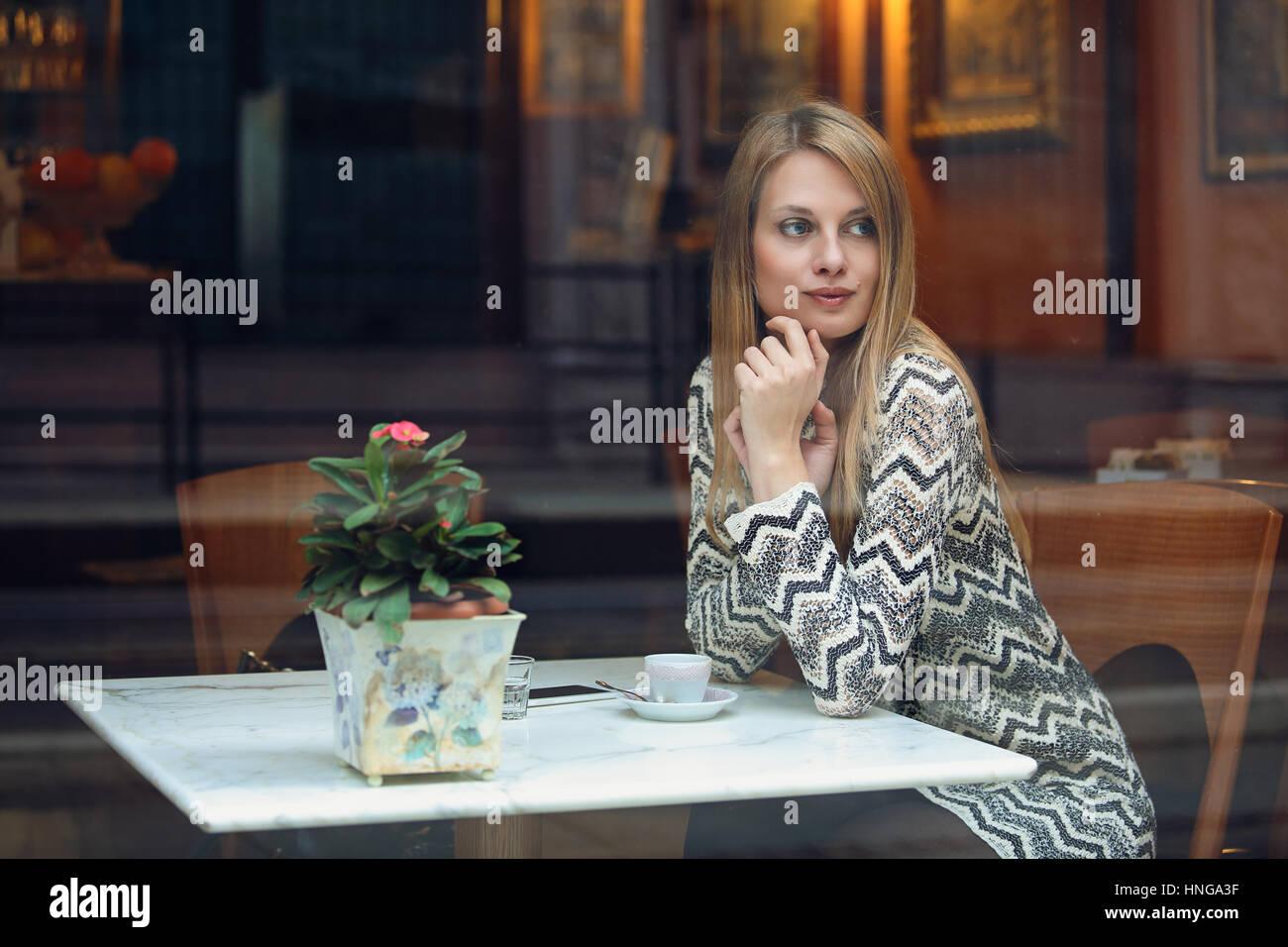 Mujer joven tomando un descanso en una elegante cafetería. El estilo de vida urbano Imagen De Stock