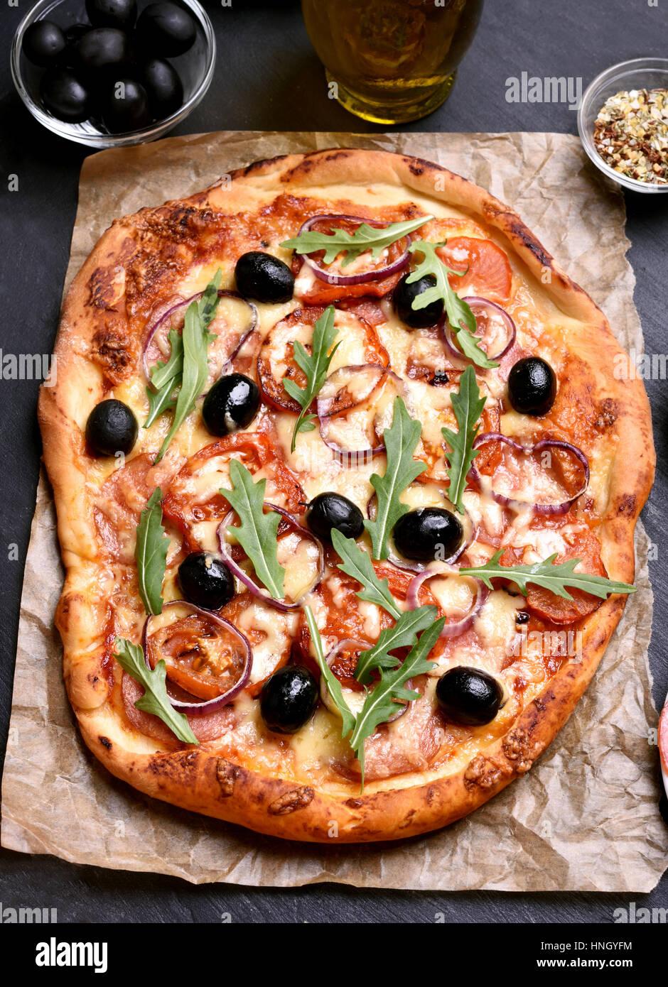 Pizza con tomate, salami y aceitunas en papel Imagen De Stock