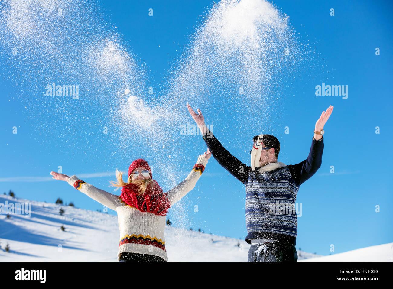 Lucha de bola de nieve. Invierno par divertirse jugando en la nieve afuera. Joven alegre feliz pareja multi-racial. Imagen De Stock