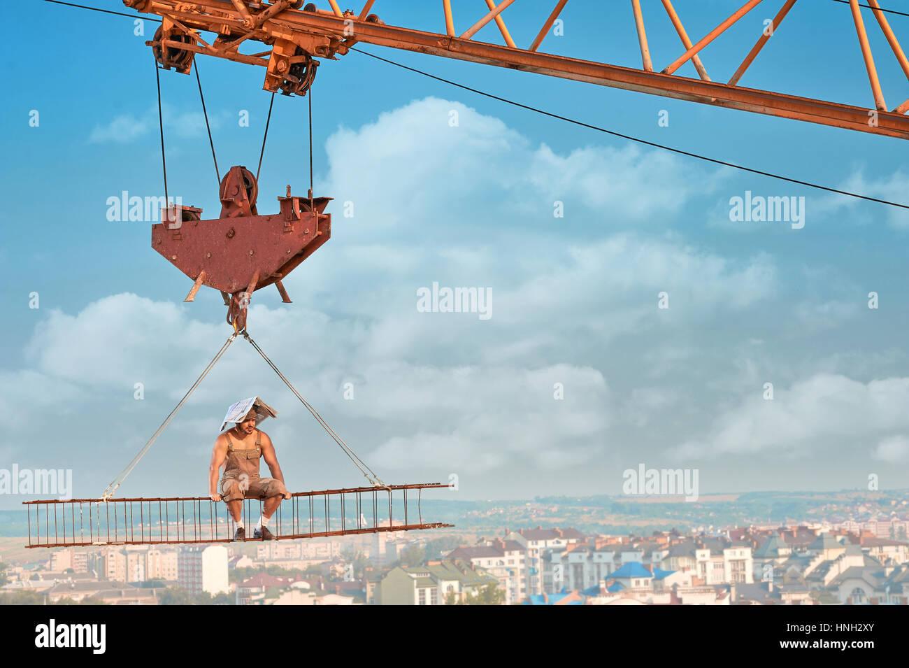 Generador muscular descansar y sentarse en construcción elevada. Imagen De Stock