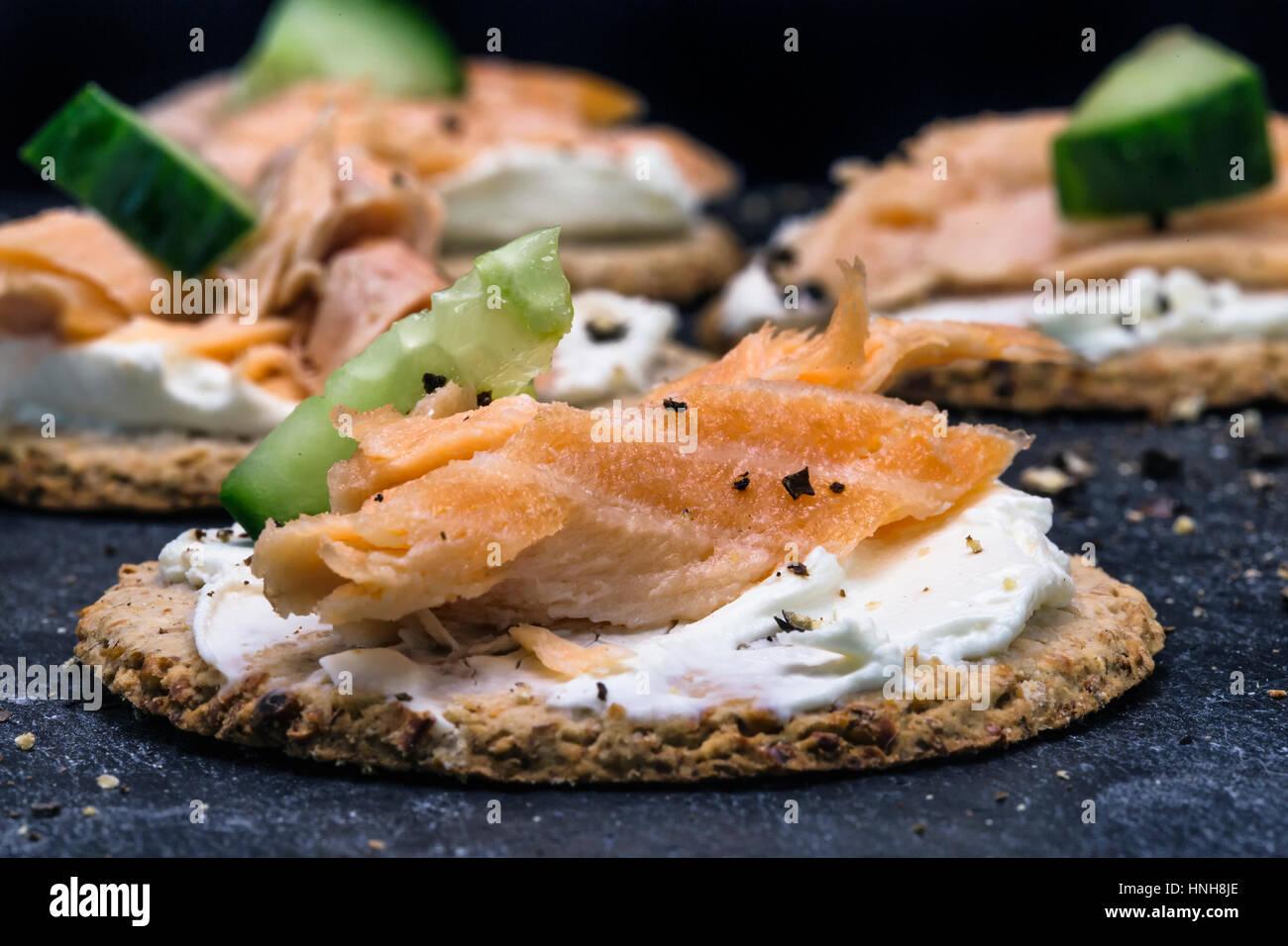 Salmón y pepino canapés en tortas de avena con negro pimienta agrietado Imagen De Stock