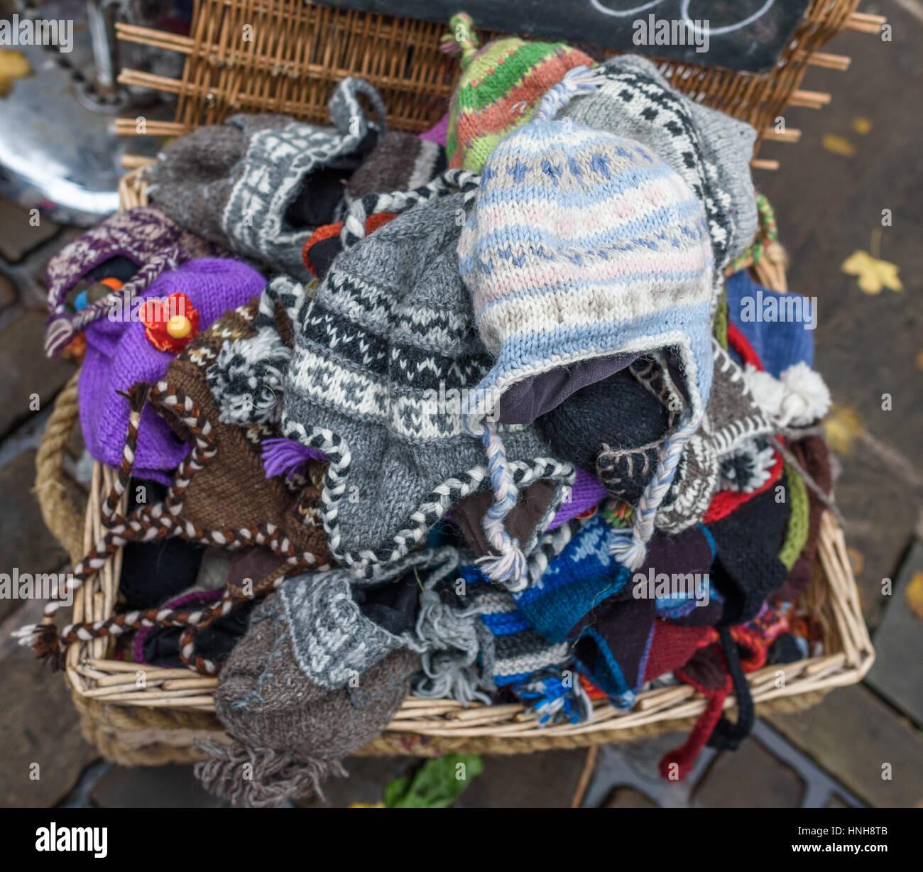 Una canasta de sombreros de lana tejida para la venta en un mercado al aire  libre c865f22487f