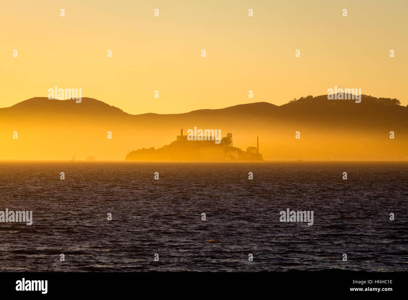 Hermosa vista de la famosa Isla de Alcatraz iluminado en el majestuoso Golden luz del atardecer al anochecer en Imagen De Stock