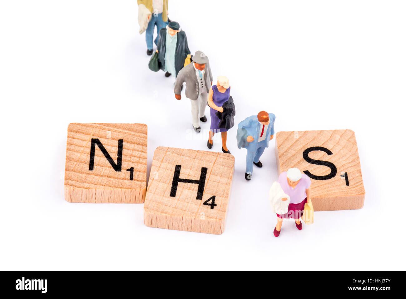 Scrabble letras componen la palabra NHS. Una línea de personas caminan entre las letras H y S. Imagen De Stock