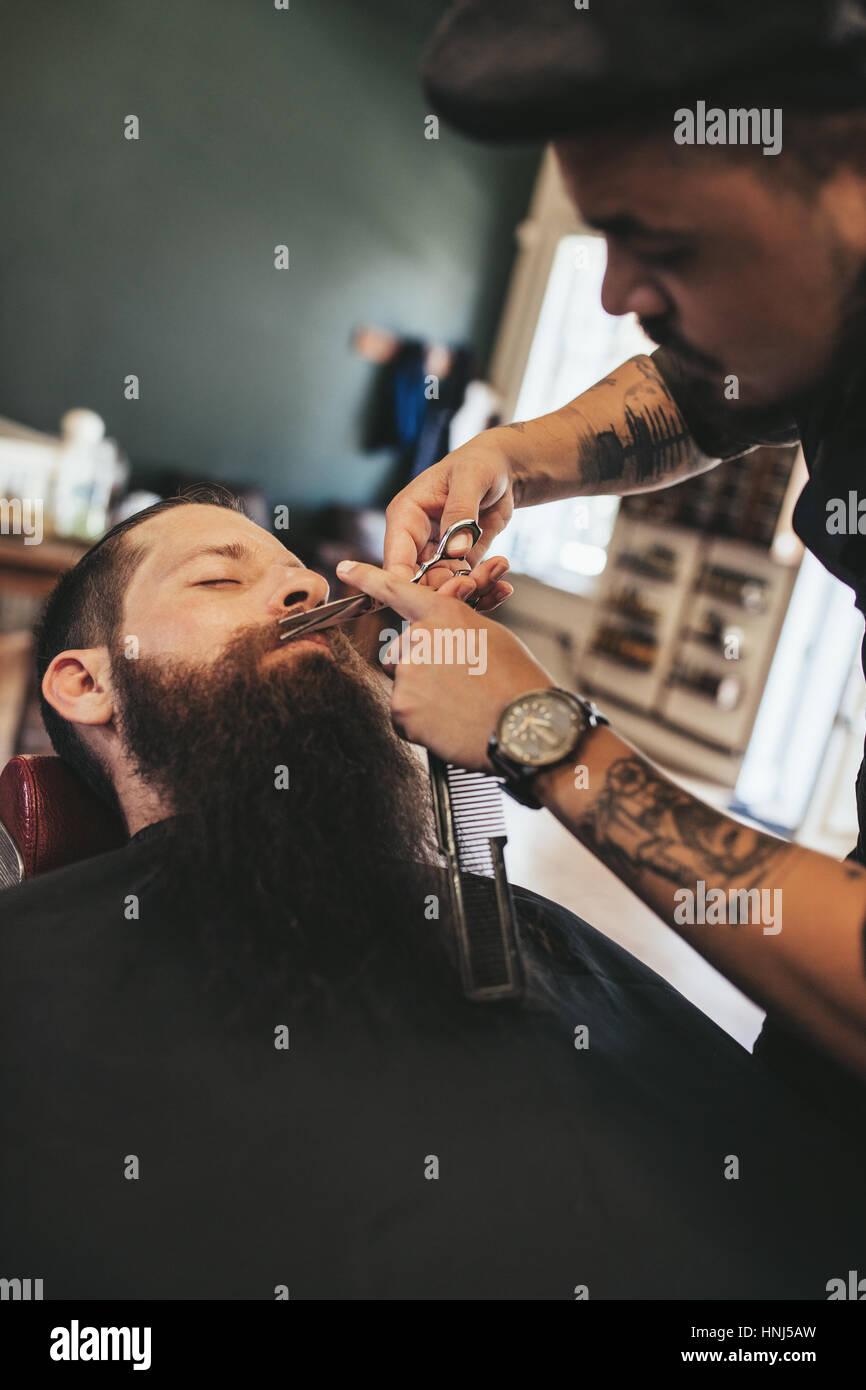 Peluquero profesional recortar el bigote de cliente en su salón. El hombre obteniendo su barba afeitada en una peluquería. Foto de stock
