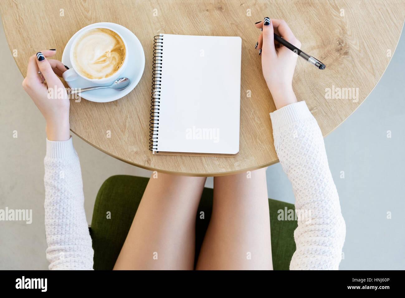 Mano de mujer escrito en el bloc de notas Imagen De Stock