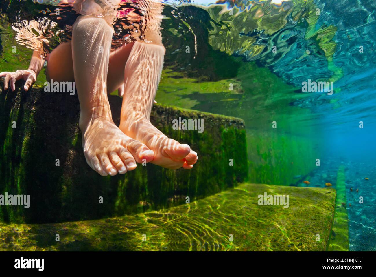 Persona feliz divertirse al borde de la piscina. Gracioso foto bajo el agua del bebé pies desnudos en la piscina Imagen De Stock