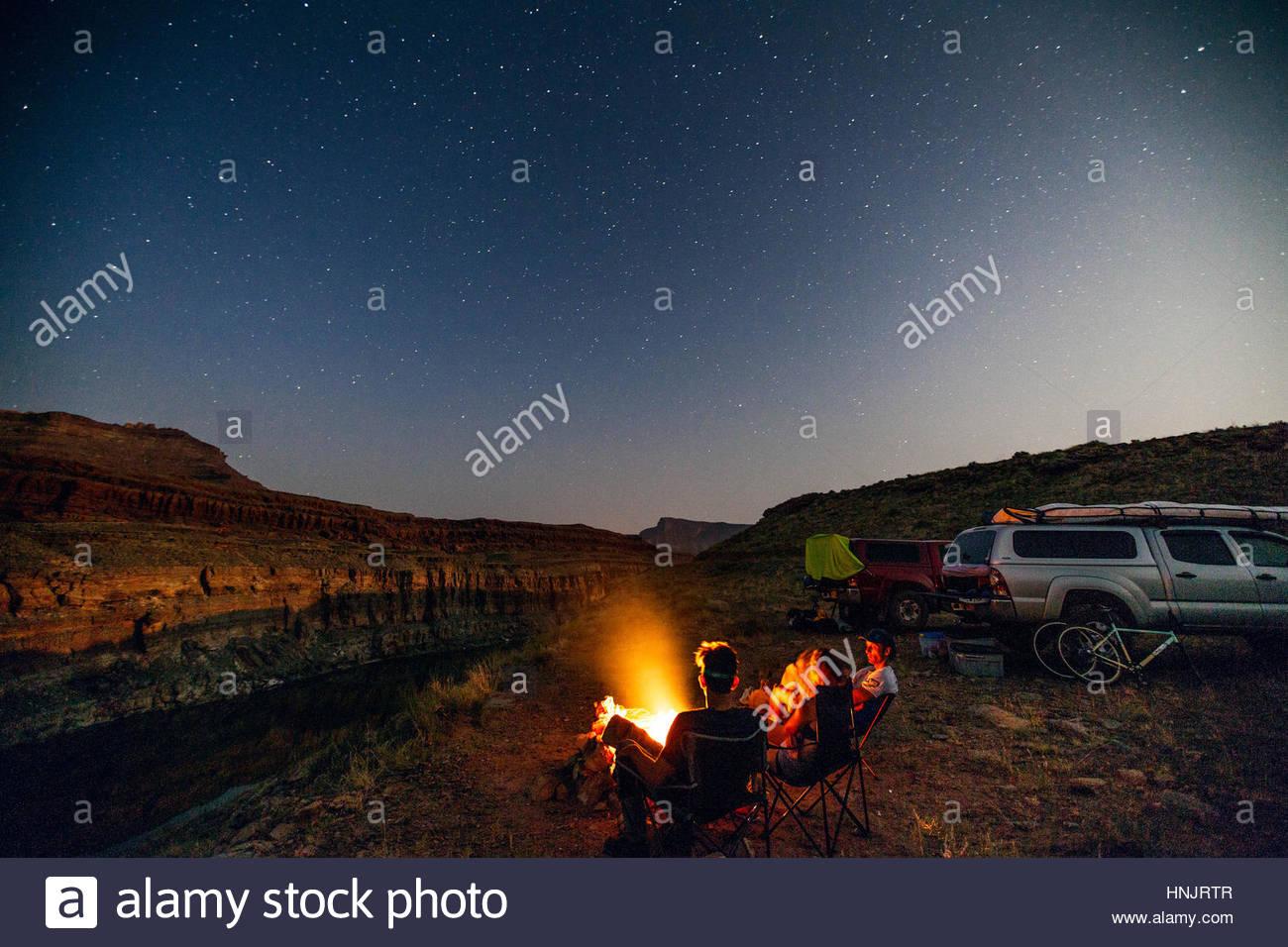 Gente acampando bajo las estrellas en las orillas de un río. Imagen De Stock