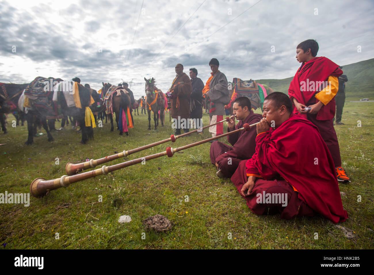 Monjes budistas tibetanos tocan los instrumentos tradicionales para bendecir a los jinetes antes de competición Imagen De Stock