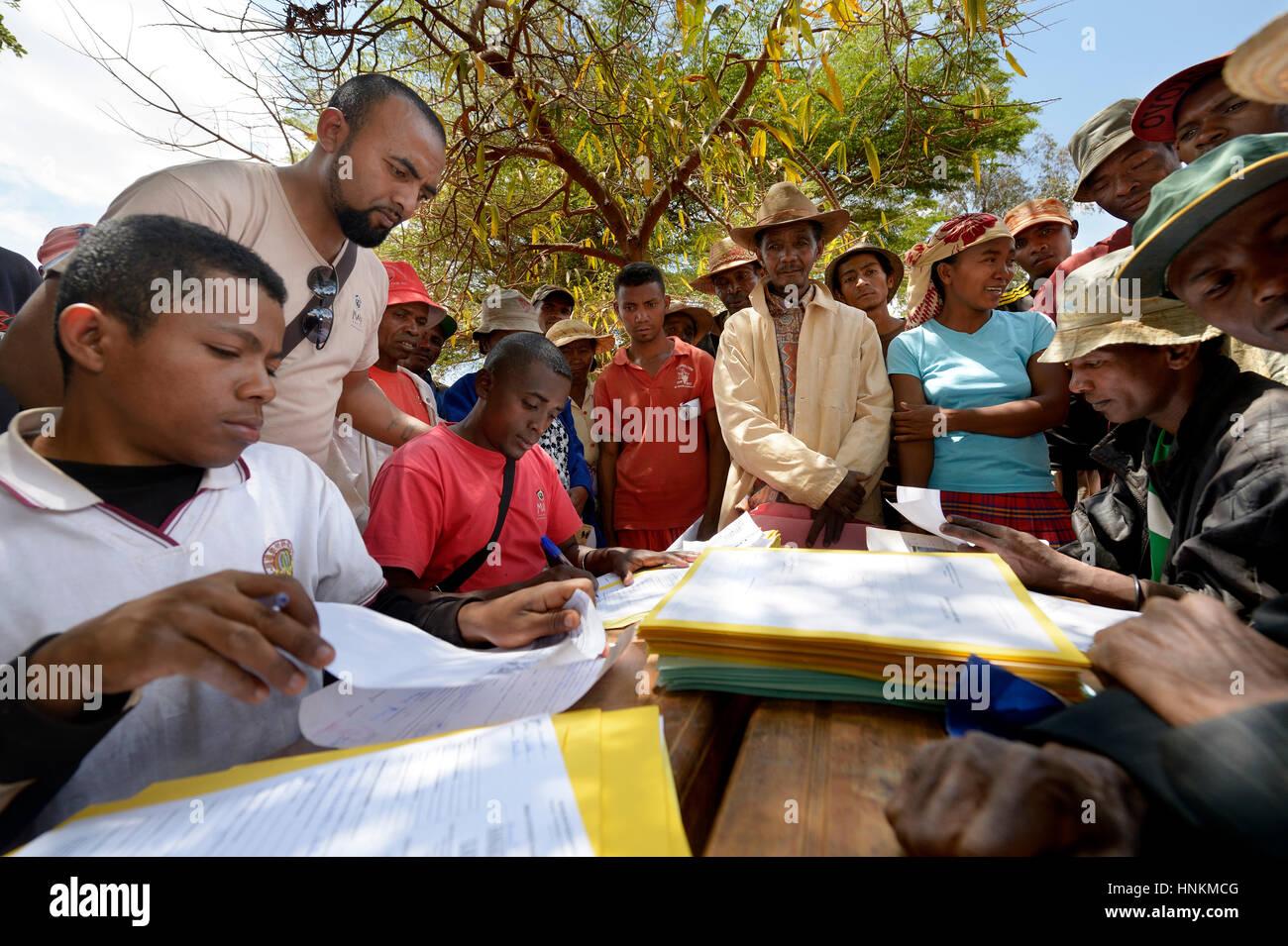 Los aldeanos llenar las solicitudes para la titulación de sus tierras en la plaza del pueblo, aldea, comuna Imagen De Stock