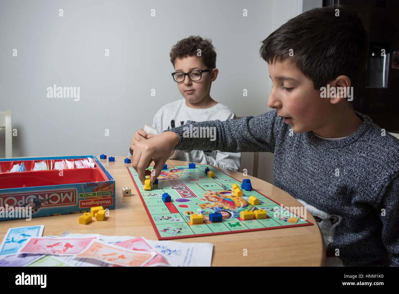 Muchachos,9-10 años,jugar monopolio juego de mesa-enfoque selectivo Imagen De Stock