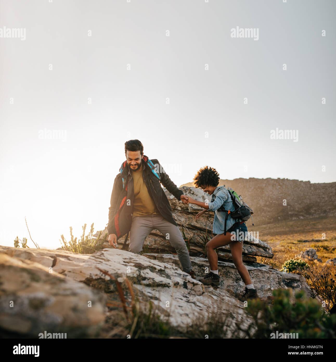Pareja joven senderismo ayudarse mutuamente en las montañas. Macho joven excursionista ayudando a una amiga mientras Foto de stock