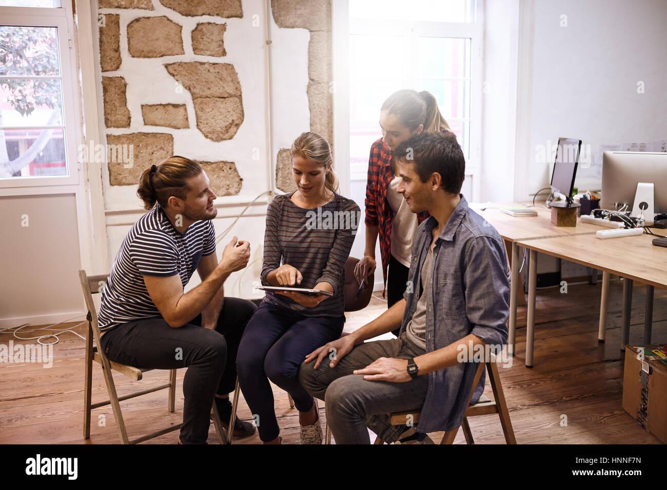 Equipo empresarial milenaria sentado y de pie en un semicírculo todos mirando cuidadosamente al Tablet PC mientras Imagen De Stock