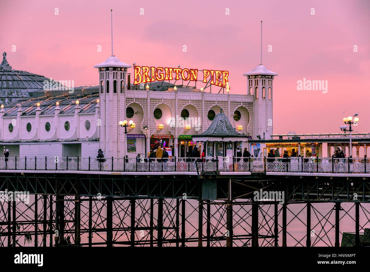 Una hermosa puesta de sol al atardecer con un cálido tono rojizo en Brighton Pier, Brighton, Inglaterra, Reino Unido Foto de stock