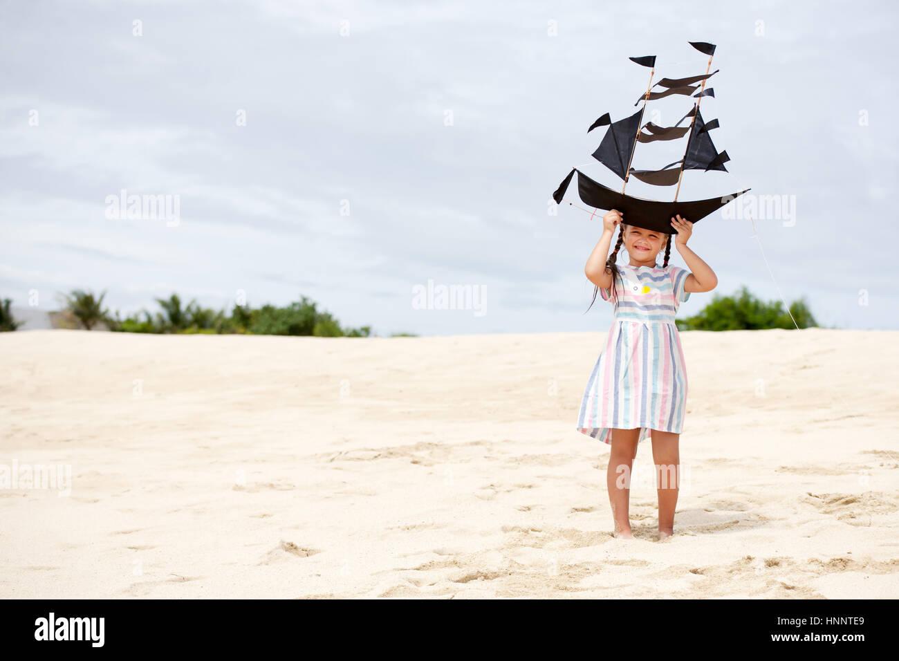 Cute Little Girl jugando en la playa, volar cometas del buque. Niño disfrutando de vacaciones familiares de Imagen De Stock