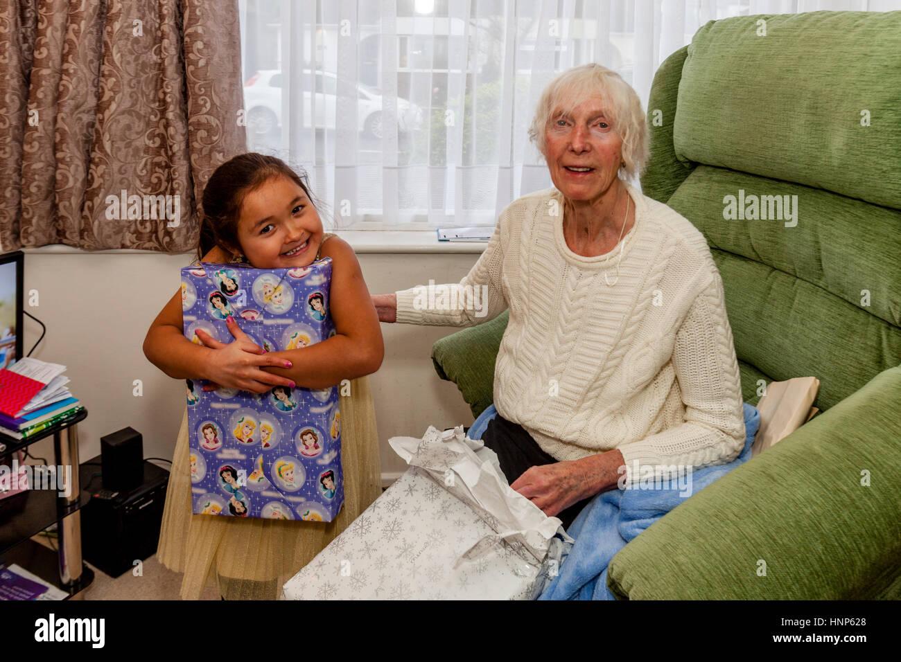 Una raza mixta y la abuela del niño abriendo regalos en Navidad, Sussex, Reino Unido Imagen De Stock