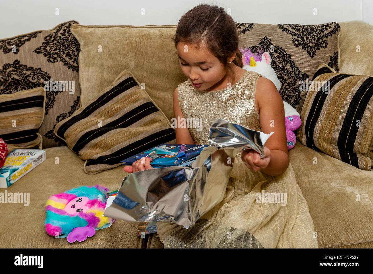 Una raza mixta niña abriendo regalos en Navidad, Sussex, Reino Unido Imagen De Stock