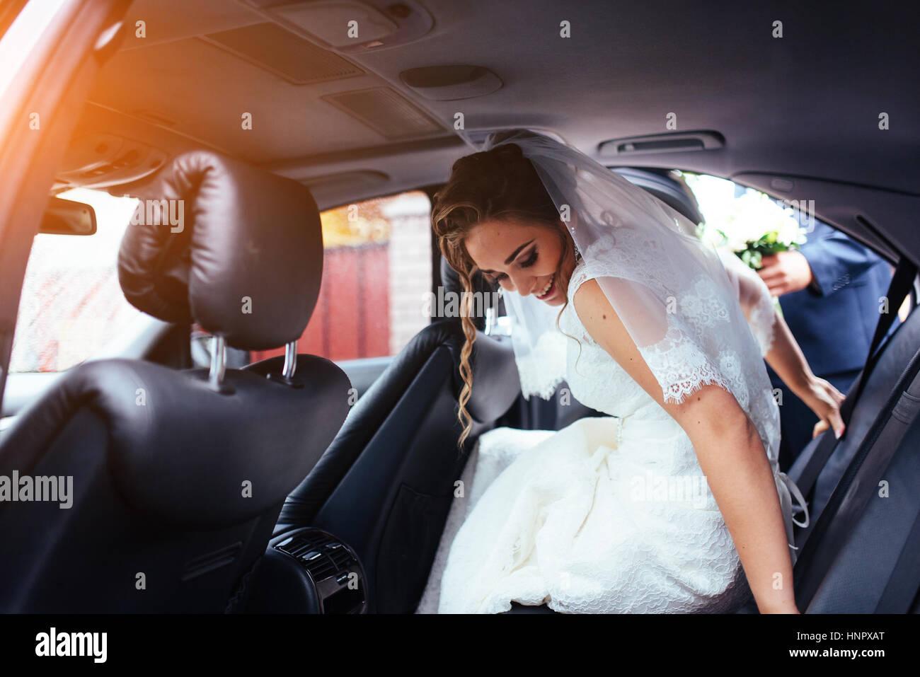 Feliz la novia y el novio cerca del coche. Imagen De Stock