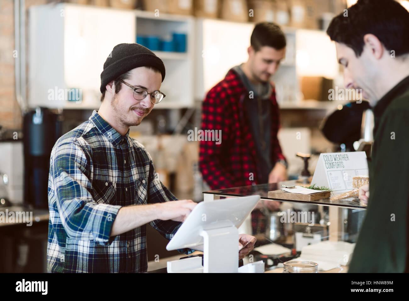 Cajero asistiendo al cliente en cafe Foto de stock