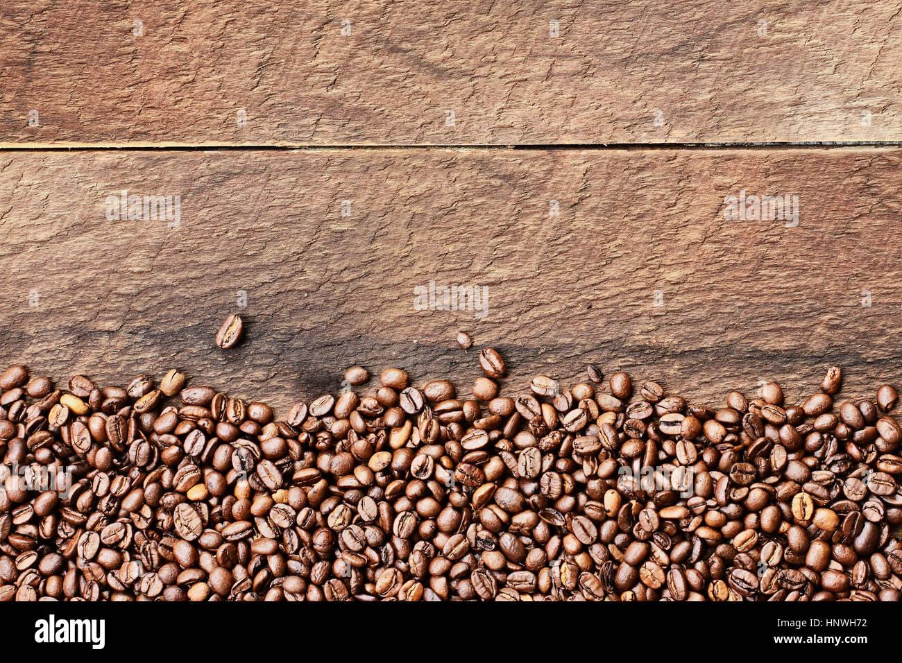 Fotografía cenital mirando hacia abajo en una imagen flatlay de granos de café sobre una tabla de madera Imagen De Stock
