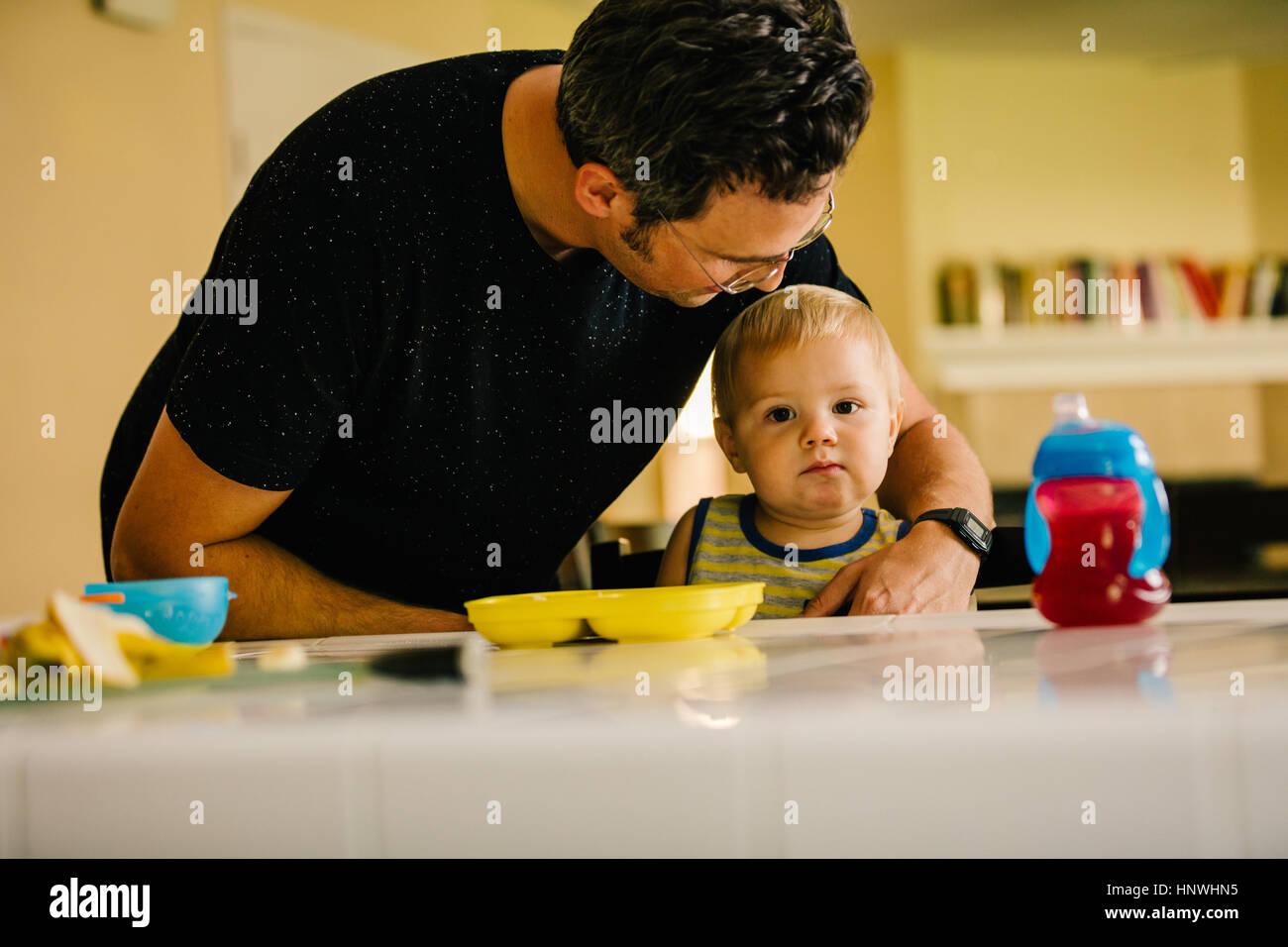 Hijo de padre ayudando a los jóvenes a la hora de la comida Imagen De Stock