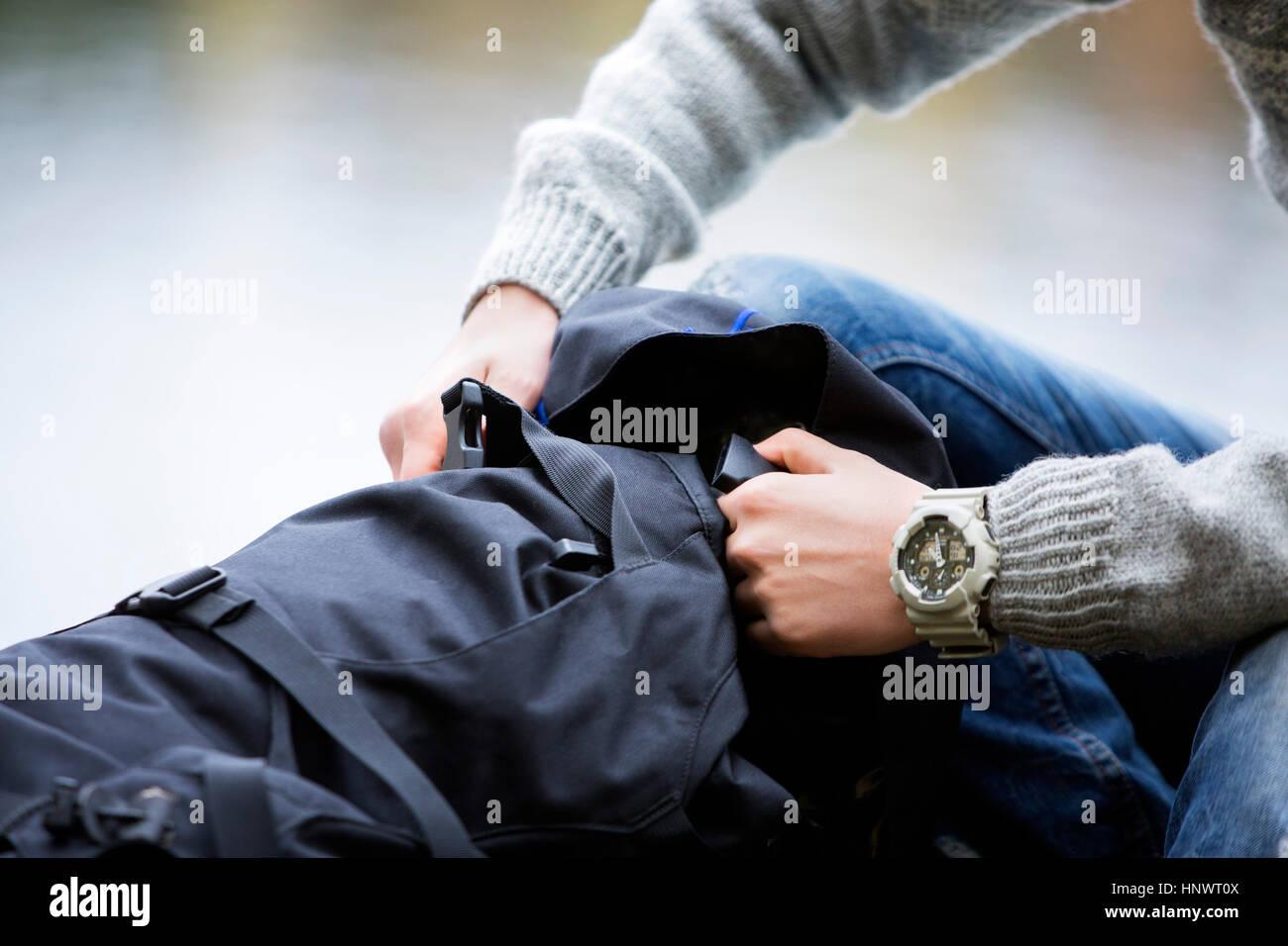 Excursionista macho apertura mochila en camping Imagen De Stock