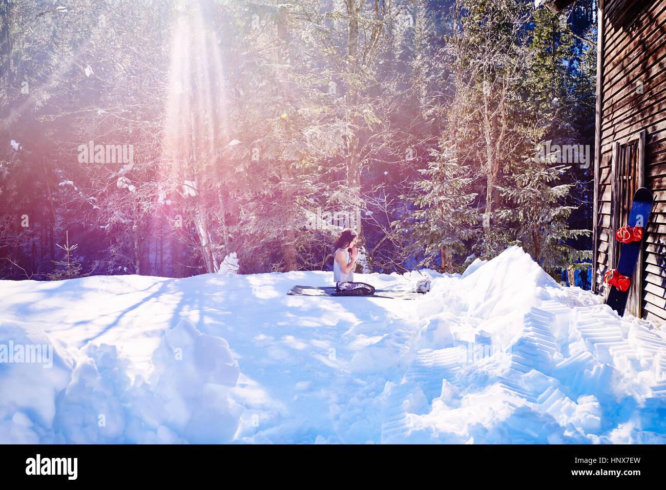 Mujer practicando yoga, arrodillado sobre la estera del yoga por cabaña en la nieve, Austria Imagen De Stock
