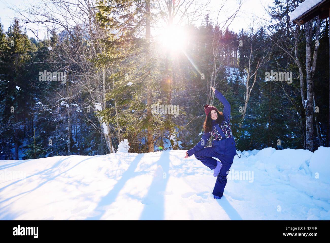 Mujer en ropa de invierno practicar yoga árbol pose en la nieve por bosques, Austria Imagen De Stock