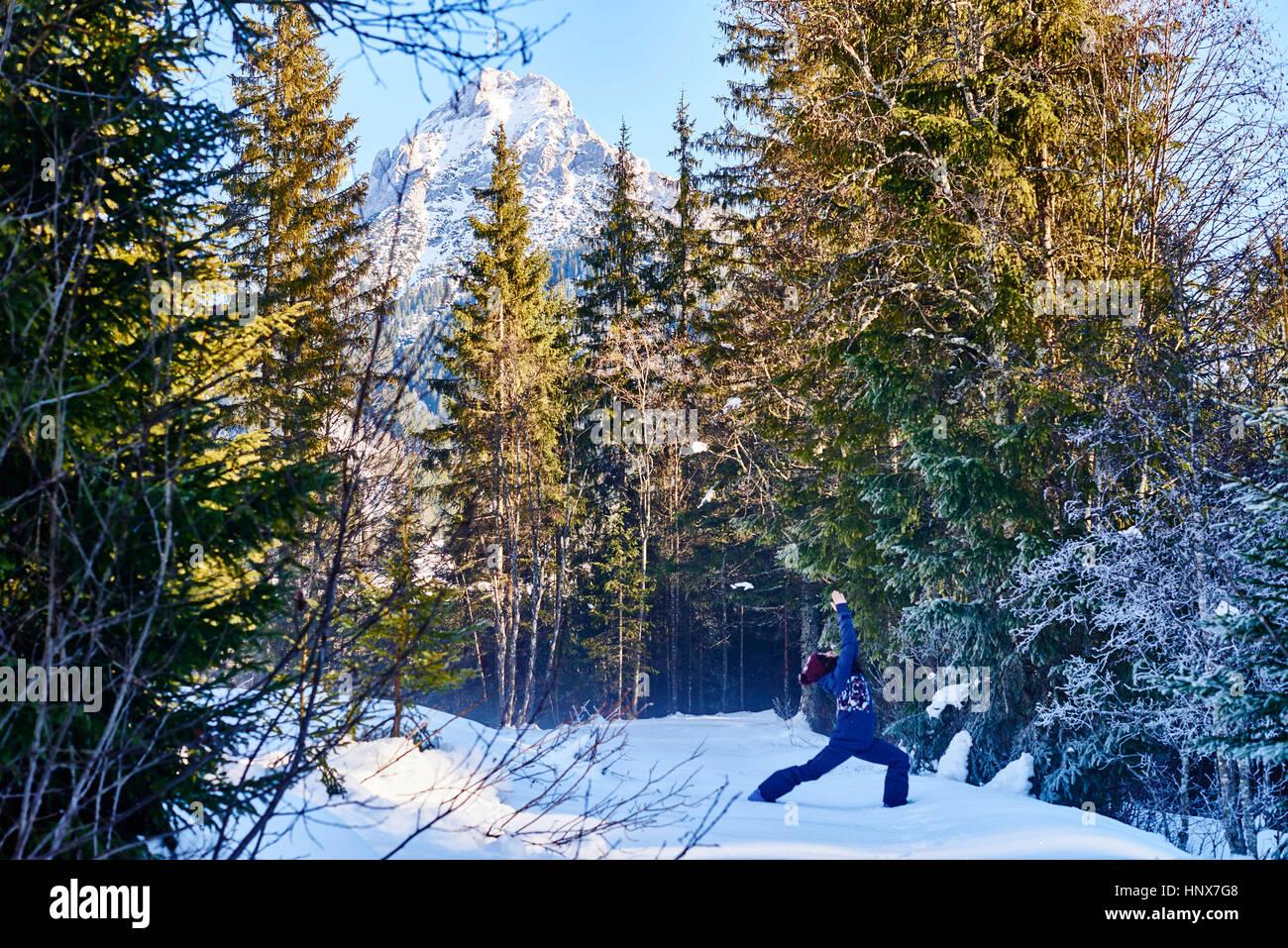 Mujer en ropa de invierno practicar yoga guerrero plantean en bosque nevado, Austria Imagen De Stock
