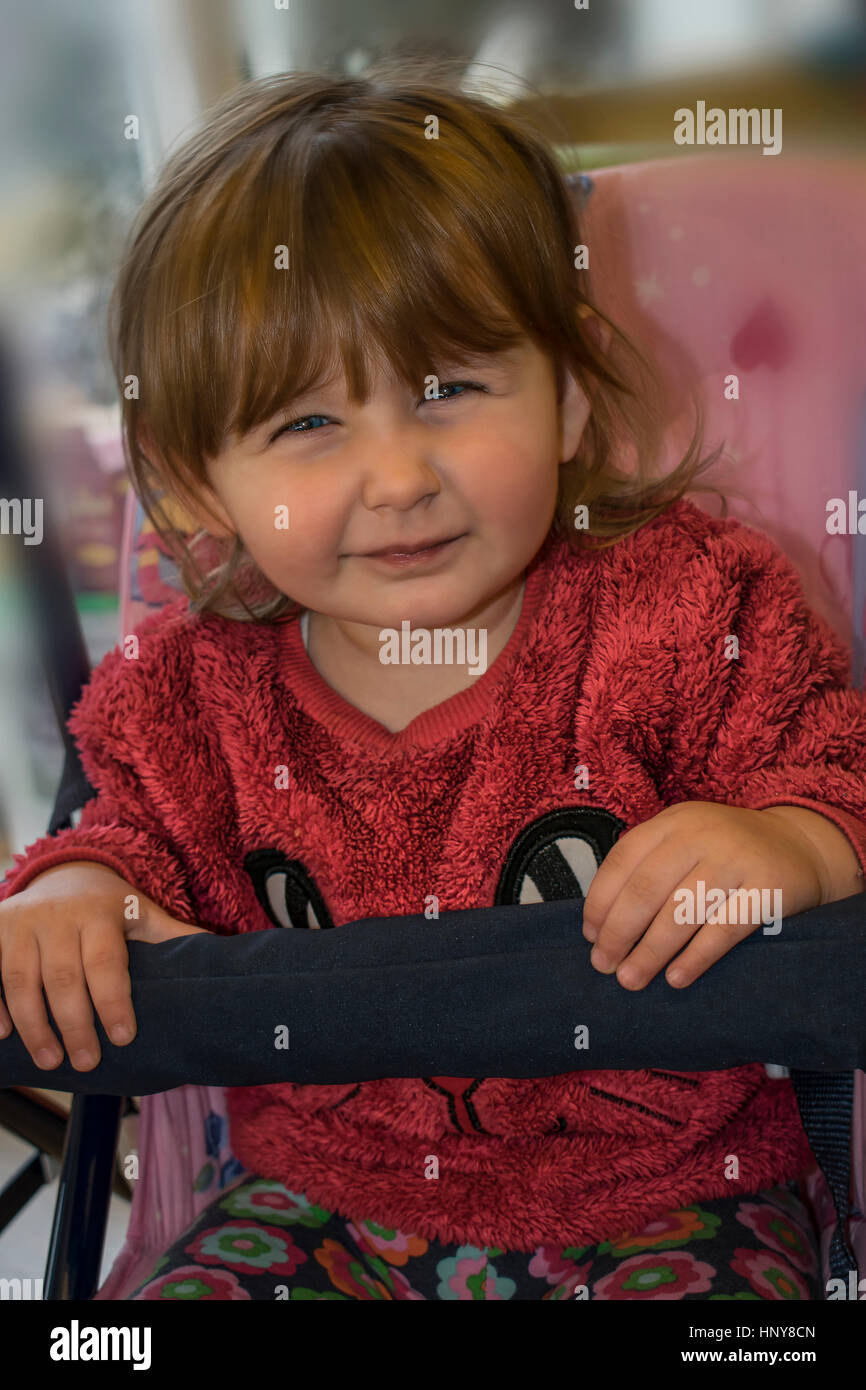 Rubia niña sentada en un columpio y vistiendo un suéter de piel rosada, mientras hace una mueca en la Imagen De Stock