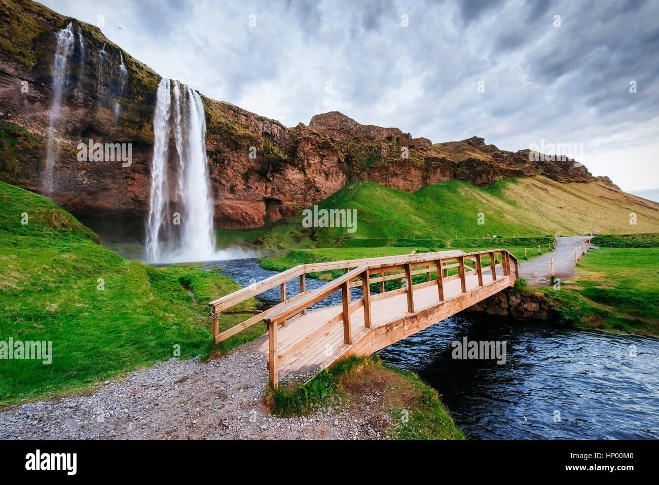 Cascada Seljalandfoss al atardecer. Puente sobre el río. Fantas Imagen De Stock