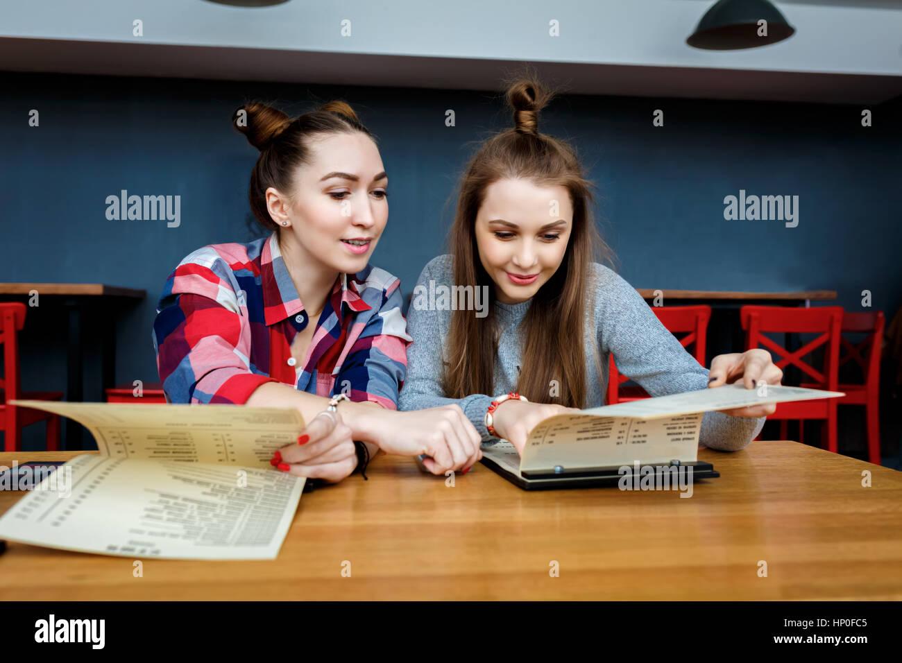 Niña alegre amigos tienen una taza de café en el moderno restaurante de la ciudad. Foto de stock