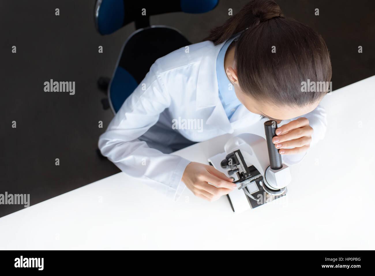 Científico que trabaja con microscopio en laboratorio Imagen De Stock