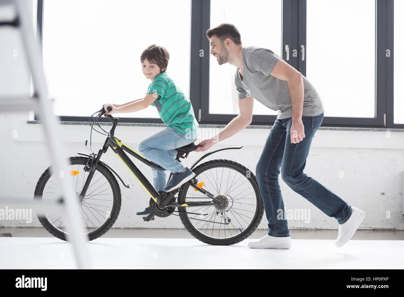 Padre joven ayudando al hijo a andar en bicicleta Foto de stock