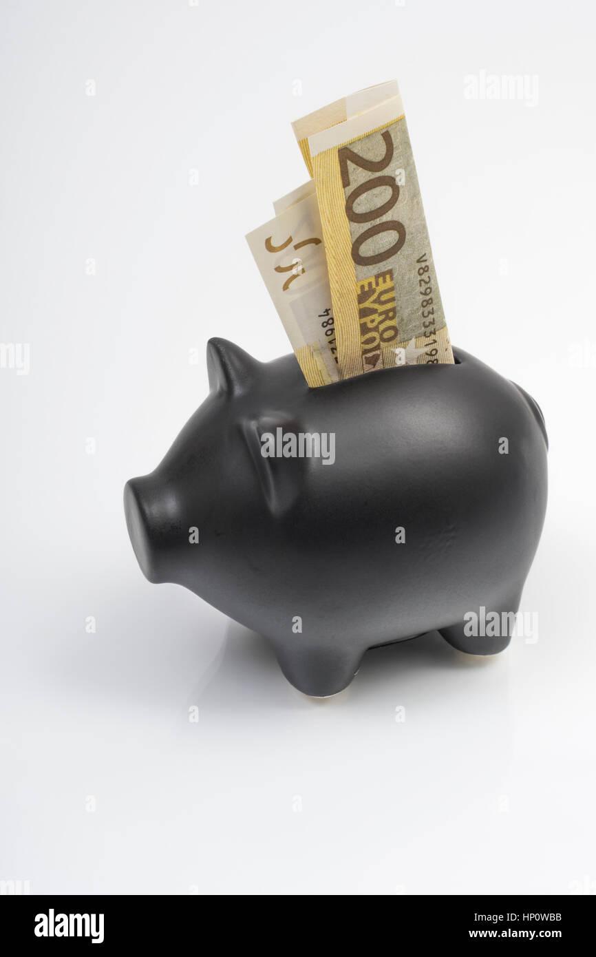 Hucha negro con billetes de 200 euros se coloca en la ranura de monedas. La metáfora de los ahorros personales, Foto de stock