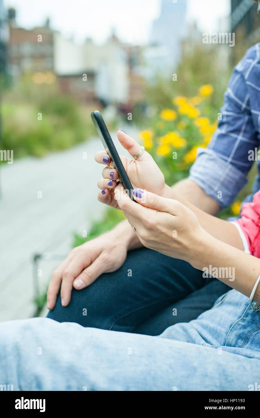 Pareja utilizando el smartphone afuera, recortadas Imagen De Stock